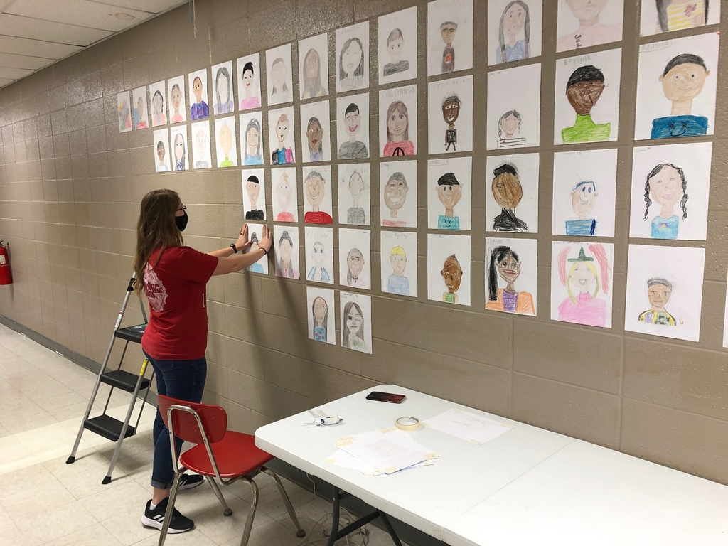 Art teacher hanging portraits in the hallway.
